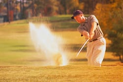 Golfer Swinging in Sand Trap